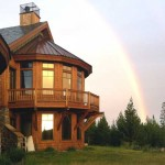 west elevation of house framed by a double rainbow